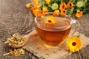 Calendula tea with fresh and dried flowers on old wooden background