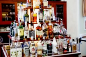 Blured view of the rack with various alcoholic drinks in the bar at modern hotel