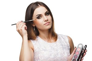 Beautiful woman with a brush for makeup and palette of eyeshadows in the hands