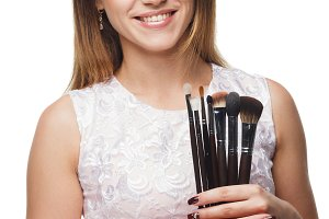 Attractive smiling woman with a set of brush for makeup in the hands