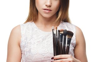 Attractive woman with a set of brush for makeup in the hands