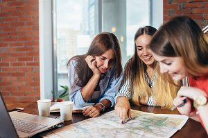 Three female students doing geography homework together at home