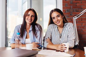 Two young female entrepreneurs sitting at work desk during the business meeting in modern conference room