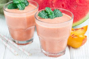 Watermelon, peach, mint and coconut milk smoothie in glass on white wooden background, horizontal
