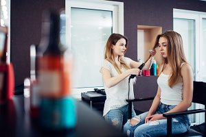 Female hairstylist straightening hair of pretty young blonde customer at hairdressing beauty salon