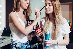 Cheerful female make-up artist applying eyeshadows on her friend eyes.