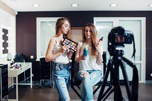 Two beauty bloggers doing make-up and haircare products review filming it on camera for their vlog