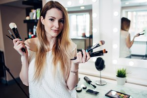 Pretty smiling woman standing with a variety of make-up brushes at beauty studio