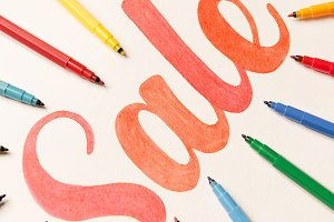 Calligraphy lettering SALE on white background between markers