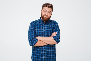 Confused frustrated bearded man standing with arms folded
