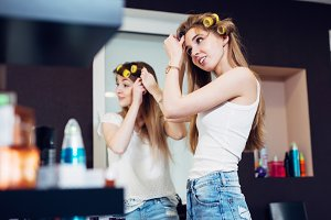 Teenager girls applying hair rollers on their long blond hair preparing to go out