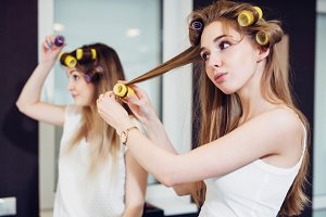 Two girls curling their hair with rollers in a room