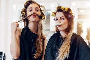 Two cute girlfriends in black cape wearing curlers making moustache out of their hair and roller in hairdressing salon