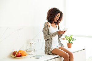 Beautiful young afro american woman texting on mobile phone