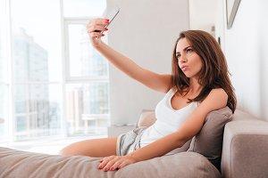 Beautiful brunette woman taking a selfie