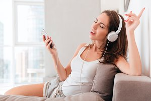 Cheerful young woman in headphones listening to music