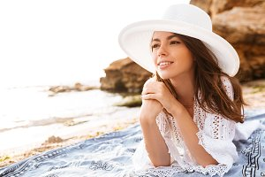 Smiling woman in hat and light summer dress