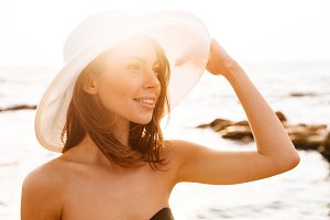Smiling woman in hat posing on beach