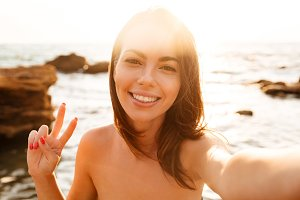 Close up image of smiling woman making selfie on beach