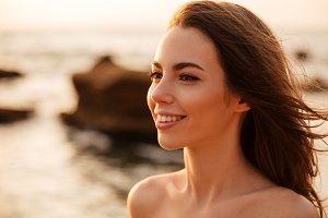 Close up image of smiling brunette woman posing on beach