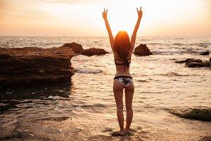 Back view of happy brunette woman in bikini