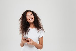 Smiling pensive woman holding smartphone in hands and looking up