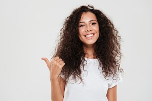 Smiling curly woman showing thumb up and looking at camera