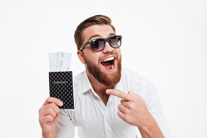 Happy young bearded man holding passport and tickets while pointing.