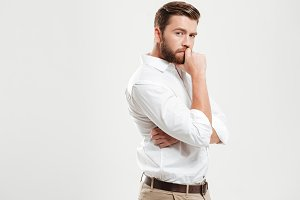 Young bearded man standing over white wall