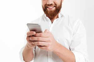 Cropped image of young bearded man chatting by phone.