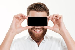 Handsome young bearded emotional man covering eyes with phone.