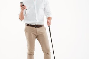 Handsome young bearded man standing over white wall with golfstick