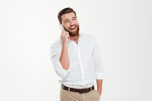 Happy young bearded emotional man talking by phone.