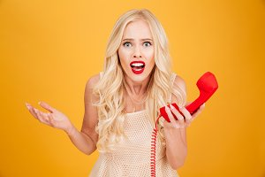 Confused young blonde woman holding telephone.