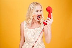 Screaming angry young blonde woman talking by telephone.