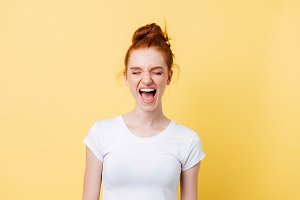 Laughing ginger woman in t-shirt with closed eyes