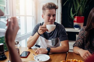 Portrait of stylish young guy holding a cup of tea having breakfast with friends in cafe