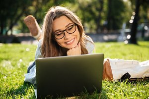 Smiling brunette woman in eyeglasses lying on grass