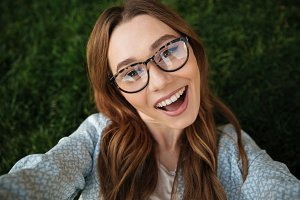 Close up top view of joyful brunette woman in eyeglasses