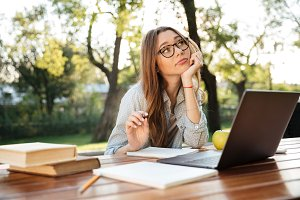 Pensive brunette woman in eyeglasses sitting by the table