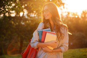 Happy brunette woman in eyeglasses hugging books