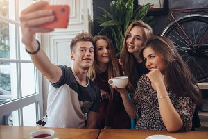 Group of cute teenagers taking selfie with cellphone while sitting in a restaurant with interior in retro style