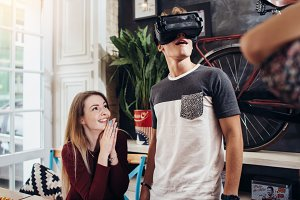 Emotional teenagers using VR headset to watch 3D films or play games hanging out at home