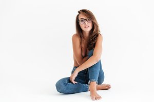 Beauty half naked woman in eyeglasses sitting on the floor