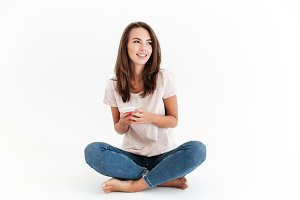 Pleased brunette woman sitting on the floor with smartphone