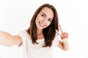Pleased woman making selfie and showing peace sign at camera