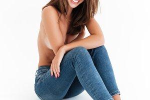Vertical image of happy half naked woman sitting on floor