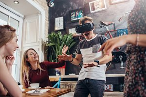 Young guy testing virtual reality headset screaming playing scary game while his cheerful pretty female friends laughing at him sitting in a cafe