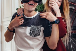 Boyfriend and girlfriend testing new vr 3d vision headset spending time together having fun laughing at home