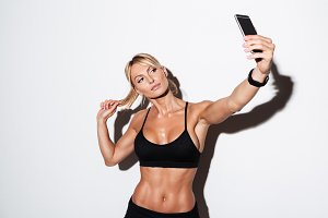 Beautiful healthy fit sportswoman taking a selfie while standing
